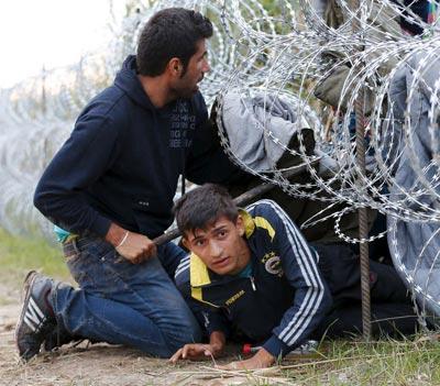 Migranti siriani passano il muro di filo spinato ungherese