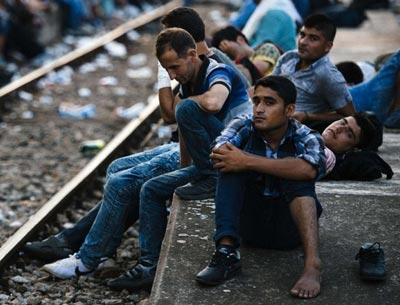 Migranti in attesa di un treno per la Serbia, presso la stazione ferroviaria di Gevgelija, sul confine macedone-greco